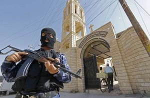 Un soldat irakien monte la garde devant une église à Bartala, à quelques kilomètres de Mossoul. Juillet 2014. Photo : AFP/Karim Sahib